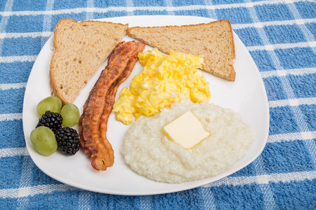 wheat toast: A traditional breakfast of scrambled eggs, wheat toast, bacon and buttered grits garnished with blackberries and grapes