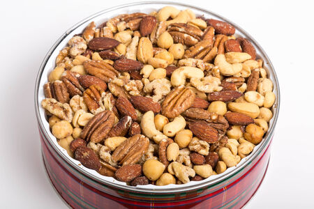 A festive red tin of deluxe mixed nuts on a white counter