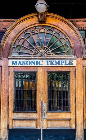 masonic: An old wooden door with iron bars on a Masonic Temple in St Johns, Canada Stock Photo
