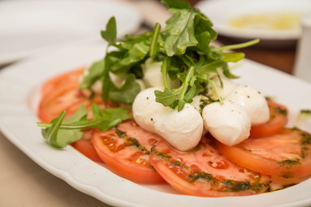 Fresh caprese salad of sliced tomatoes, mozzarella cheese wtih basil and olive oil Imagens