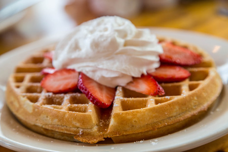 Golden brown waffle topped with sliced strawberries and whipped cream