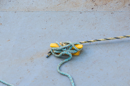cleat: A frayed old blue rope tied to a yellow cleat on a concrete pier Stock Photo