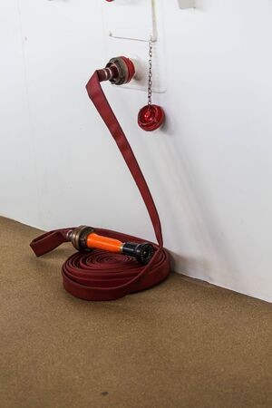 bulkhead: A red fire hose by a white bulkhead on a ship