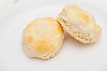 flaky: Two hot, fresh, flaky, baked biscuits on a white plate