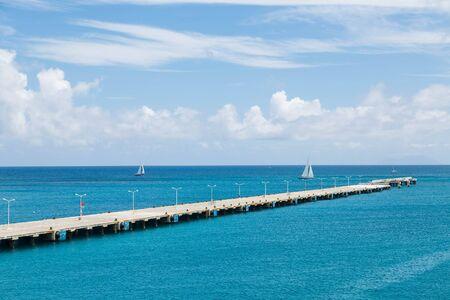Concrete pier extending far into clear aqua water of the Caribbean