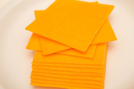 Sliced cheddar cheeses on a white plate