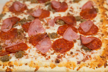 gourmet pizza: Hot gourmet pizza with pepperoni, sausage, ground beef and ham Stock Photo