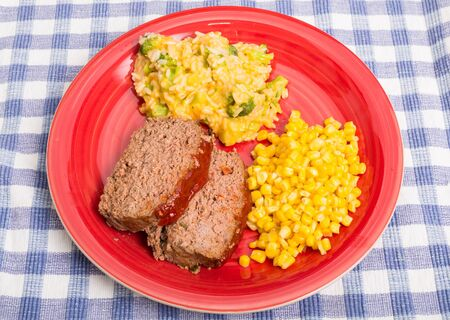Sliced meatloaf, corn and cheesy broccoli rice on a red plate on a blue plaid mat Stock Photo