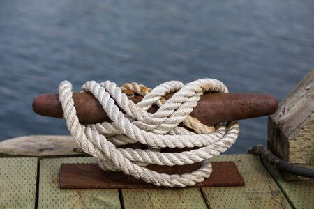 cleat: White rope secured to an old rusty cleat on a wood pier