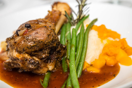 Roast lamb shank pn plate with green beans, mashed potatoes garnished with rosemary