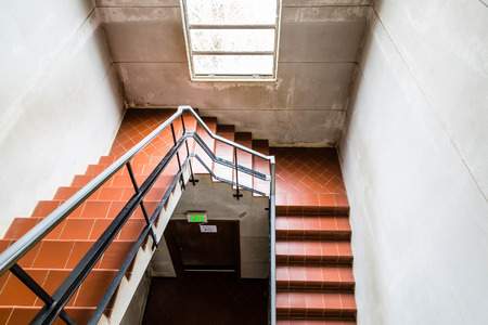 stairwell: Staircase in cement stairwell with quarry tile steps and black iron railings