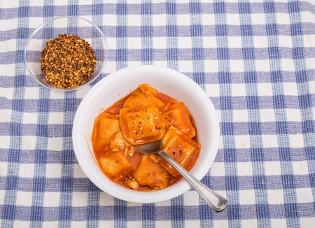 pepper flakes: Canned ravioli in a white bowl on blue plaid tablecloth with red pepper flakes Stock Photo