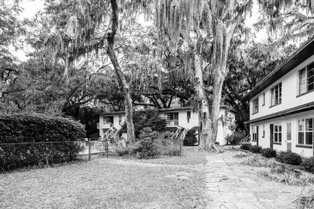 An old deserted and closed white cinder block and green motel under southern oaks and spanish moss