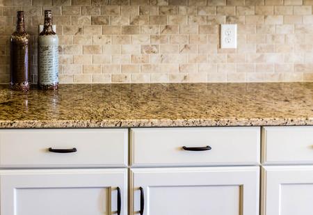 花こう岩のカウンター トップと近代的な空キッチン
