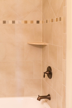bronzed: Modern tile bathtub and shower with bronzed fixtures Stock Photo