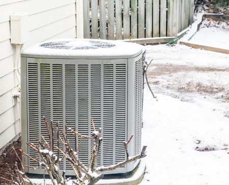 A residential air conditioner unit in the snow in winter