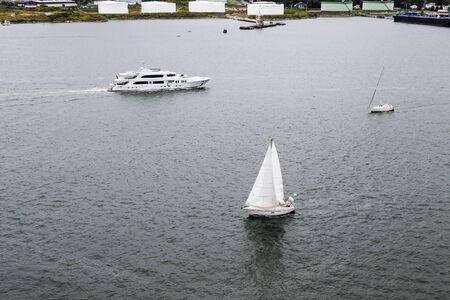 fuel tanks: White Sailboats and Luxury Yacht in Calm Blue Bay past white fuel tanks Stock Photo