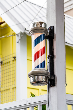 An old fashioned barber pole on a wood post outside a yellow cabana