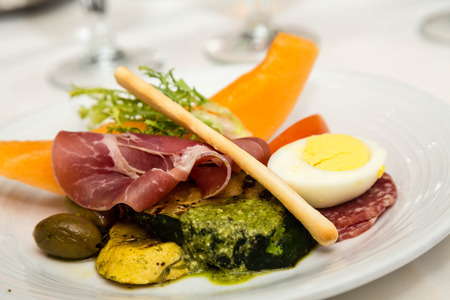 breadstick: Plate of antipasti with breadstick, boiled egg, and pesto sauce