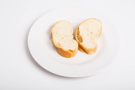 crusty french bread: Two pieces of crusty french bread on a white plate