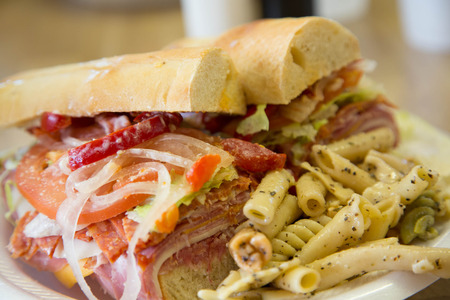 french roll: An italian sub sandwich on french roll with fresh pasta salad