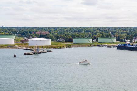 fuel tanks: A luxury pleasure boat past fuel tanks on the shore