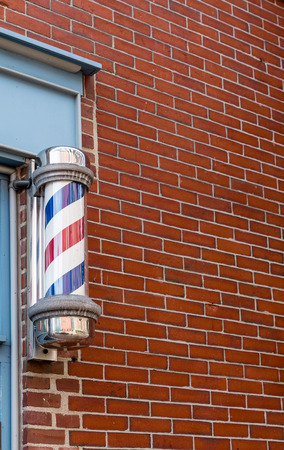 barber: An old fashioned barber pole by a red brick wall Stock Photo