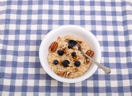 A bowl of oatmeal with fruit on a blue placemat Stock Photo