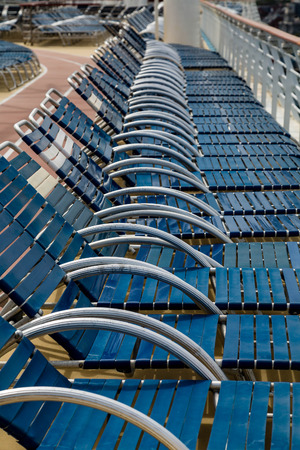 lounges: Row of blue chaise lounges on the deck of a cruise ship