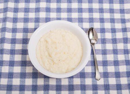 grits: A bowl of white corn grits on a blue plaid placemat