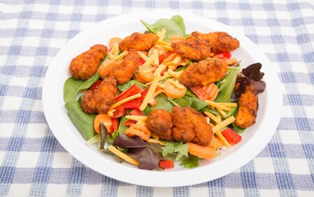 tenders: A fresh spinach salad with carrots, cheese, and red bell pepper topped with buffalo chicken tenders