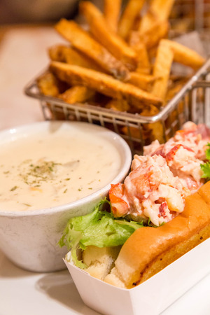 french roll: Traditional Lunch in Bar Harbor, Maine of Lobster roll, lobster bisque and french fries