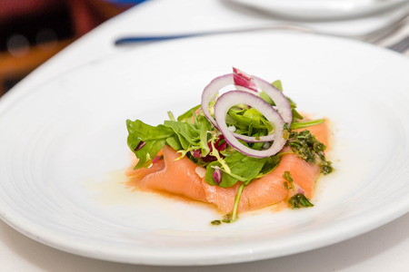 An appetizer of smoked salmon, arugula and sliced onion Imagens