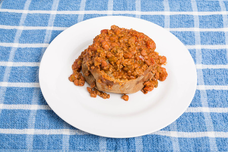 A hot baked potato in white plate smothered in spici chili with beans and meat