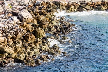 seawall: An iron pipe in a rock seawall over blue sea Stock Photo