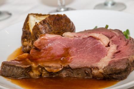 Enorme plaat van zeldzame rundvlees met jus en gebakken aardappelen Stockfoto