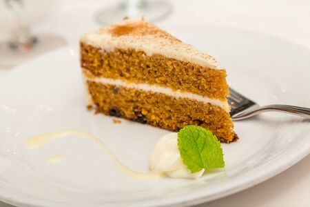 dollop: Slice of carrot cake on a white plate with dollop of whipped cream and mint leaf