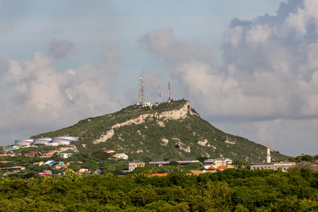 telecomm: Telecomm equipment on a tropical hill over homes and industry