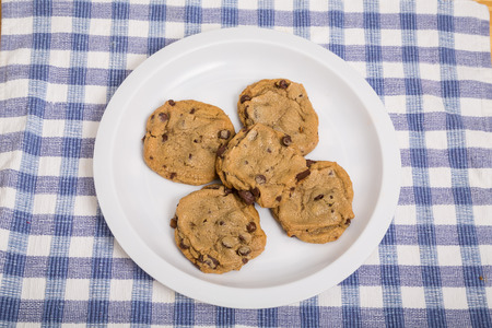 blue plaid: A white plate of fresh baked chocolate chip cookies on blue plaid towel