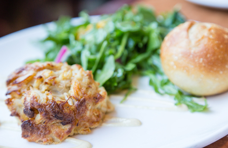 dungeness: Fresh dungeness crab cake on white plate with green salad and roll in window light Stock Photo
