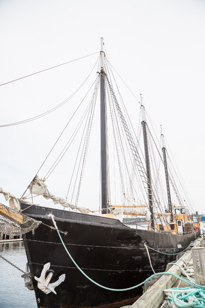 An old wood, three masted schooner with a white traditional anchor Stock Photo