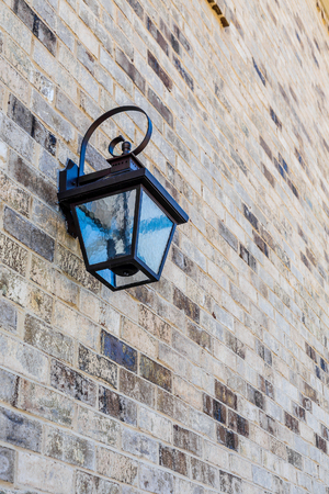 sconce: A classic black iron light fixture on a brick wall Stock Photo