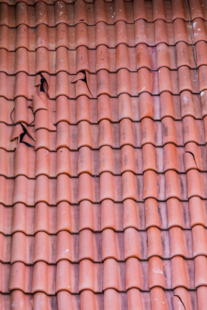 damaged roof: Broken clay tiles on a red roof
