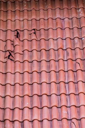 Tejas de barro rotos sobre un techo rojo