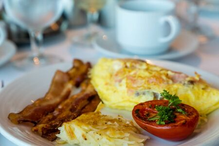 broiled: A fresh Omelet of smoked salmon and cheese with Bacon Hash Browns and Broiled Tomato.jpg Stock Photo