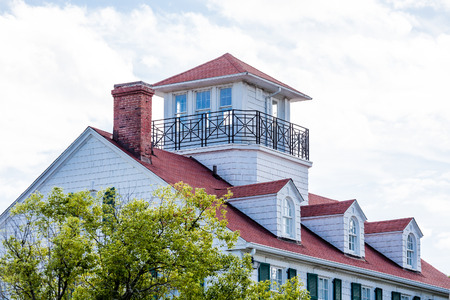 Classic white home with red roof, dormers and widows walk photo
