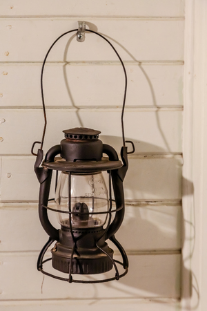 An old antique oil lamp hanging on a wood wall
