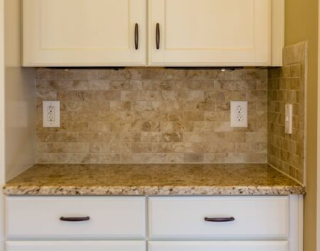 kitchen countertops: Granite countertops and tile backsplash on white cabinets in new modern kitchen