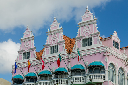 Colorful building in Aruba with pink stucco, flags and green awnings photo
