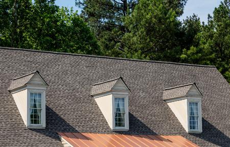 古い灰色の鉄片屋根の上 3 つの白い木製 dormers
